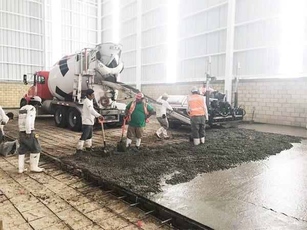 imagen de constructores haciendo colado de cemento dentro de bodega industrial