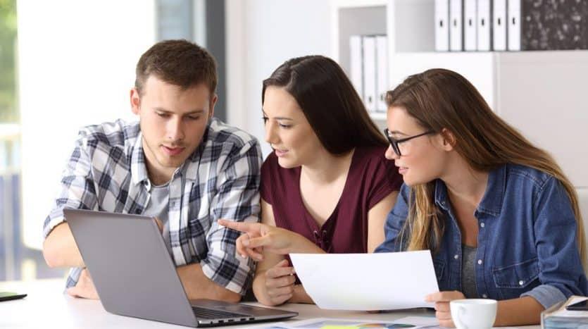 imagen de tres personas usando una laptop