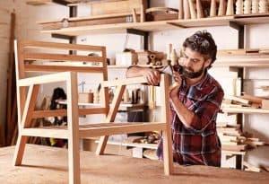 imagen de empresario tallando una silla de madera