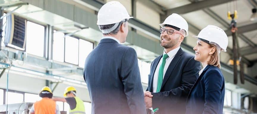 imagen de tres personas formales con cascos industriales