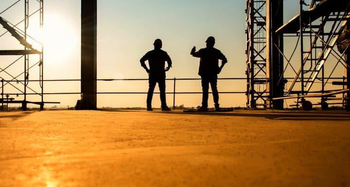 imagen de dos constructores con fondo de construcción