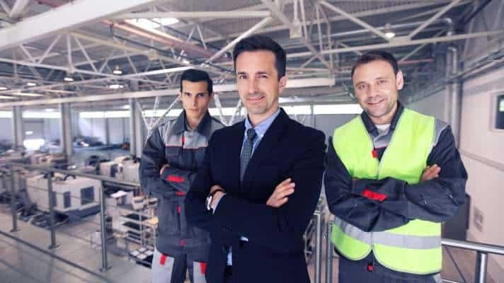 imagen de tres personas con ropa de trabajo fondo industrial