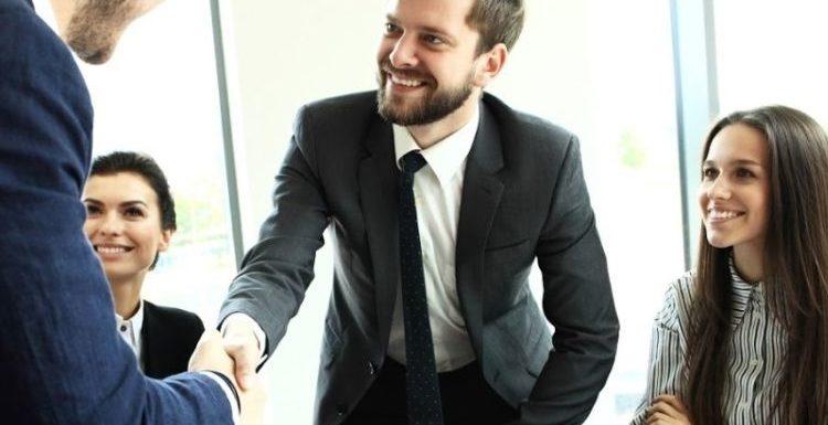 personas de negocios cerrando un trato con un apreton de manos en medio de una equipo de trabajo