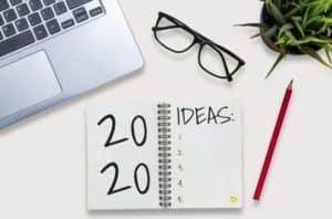lista de ideas 2020 escrito sobre libreta, laptop, gafas, lápiz, maceta con planta sobre escritorio
