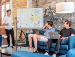 Equpo de trabajo reunido revisando etapas de proyecto en pizarrón con notas. Dos hombres sentado en sillón