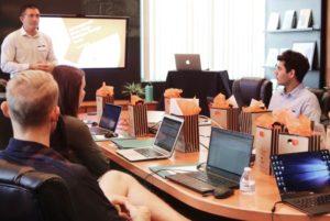 Junta en sala de juntas con equipo de trabajo poniendo atención al ponente al frente. escrotiorio con pc, cañon de diapositivas.