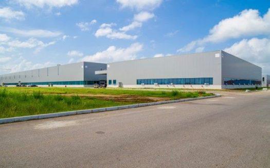 parque industrial visto desde afuera, terreno area verde, cielo azul, bodega industrial al fondo